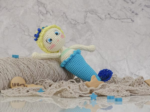 beautofull little mermaid with a blue starfish and golden hair