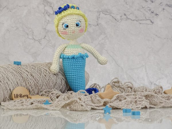 beautofull little mermaid with a blue starfish, with golden hair and blue eyes